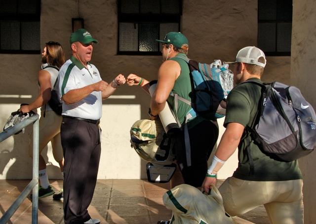Coach Walsh fist bumps captain Sullivan Grosz