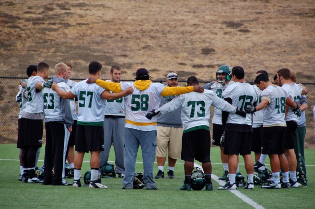 The defensive line meets with Coach Ena after practice