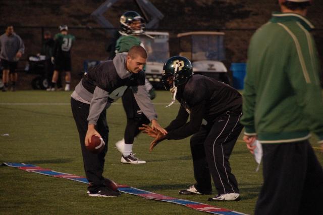 Quarterback Dano Graves hands off the ball to quarterback Chris Brown