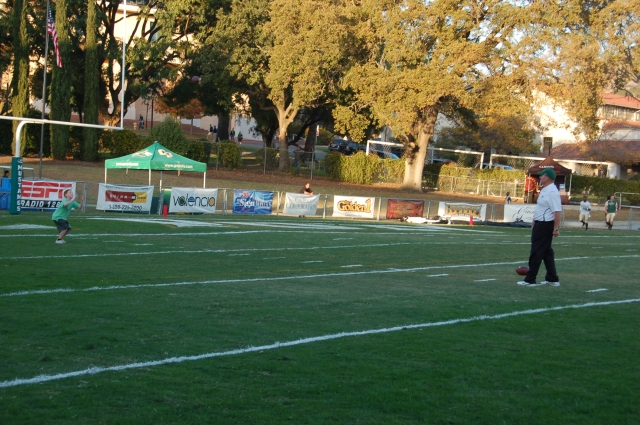 Coach Walsh plays catch with a young boy on the field before the game